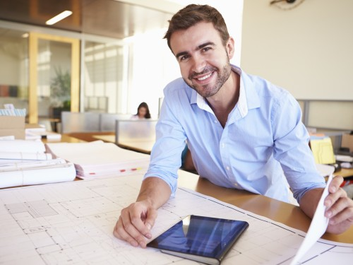 Male Architect With Digital Tablet Studying Plans In Office